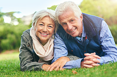 Buy stock photo Portrait of a happy senior couple lying down on the grass together in the park