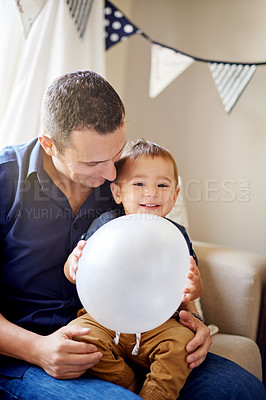 Buy stock photo Shot of a father celebrating his son's first birthday at home
