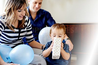 Buy stock photo Shot of an adorable little boy opening presents with his mother and father on his first birthday
