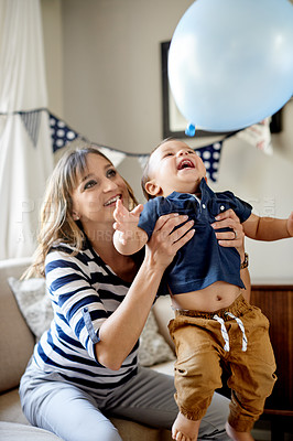 Buy stock photo Shot of a mother and son playing with a balloon on his first birthday at home