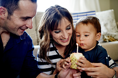 Buy stock photo Shot of an adorable little boy having a cupcake on his first birthday with his parents at home