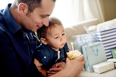 Buy stock photo Shot of an adorable little boy having a cupcake on his first birthday with his father at home