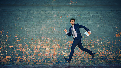 Buy stock photo Shot of a young corporate businessman jumping midair against a brick wall