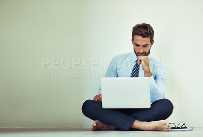 Buy stock photo Shot of a young corporate businessman sitting on the ground with a laptop