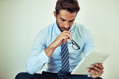 Buy stock photo Shot of a young corporate businessman sitting with a digital tablet
