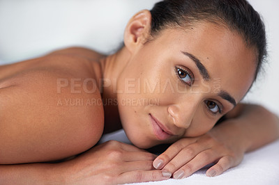 Buy stock photo Portrait of a beautiful young woman relaxing on a massage table at a spa