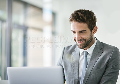 Buy stock photo Cropped shot of a handsome young businessman working on a laptop in an office