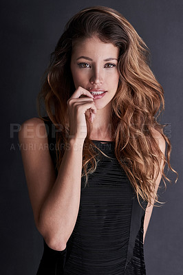 Buy stock photo Studio portrait of a seductive young woman posing against a dark background