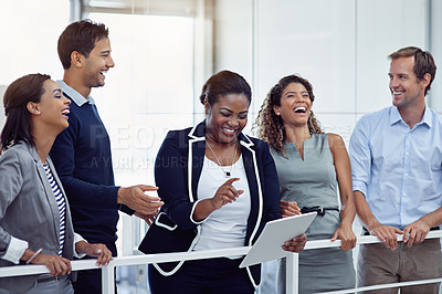 Buy stock photo Shot of a group of laughing colleagues working together on a digital tablet in an office