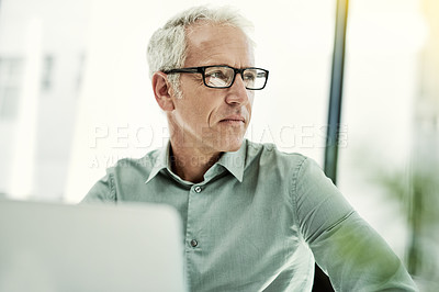 Buy stock photo Shot of a mature businessman working on a computer at his desk in an office