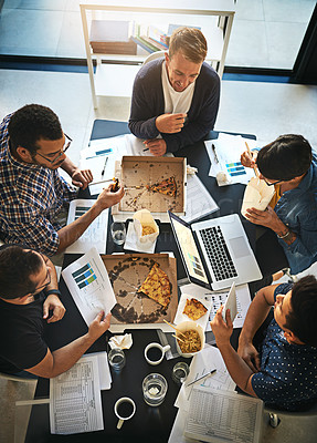 Buy stock photo Shot of a group of colleagues eating while having a meeting in the boardroom