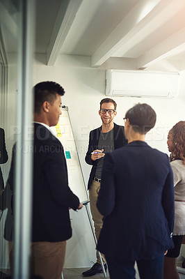 Buy stock photo Shot of a young man giving a presentation to colleagues in an office