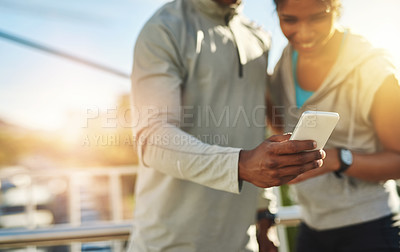 Buy stock photo Shot of a young sporty couple using a cellphone outside