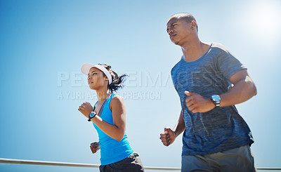 Buy stock photo Shot of a young sporty couple out for a run together