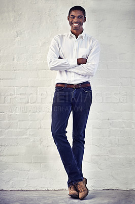 Buy stock photo Shot of a casually dressed young man standing against a brick wall