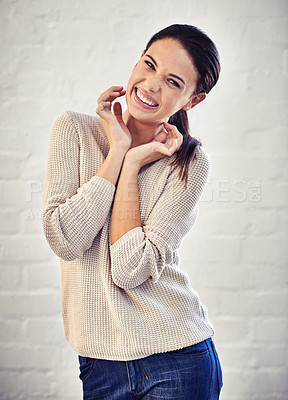 Buy stock photo Portrait of a young woman smiling sweetly against a brick wall