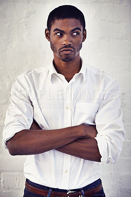 Buy stock photo Shot of a serious young man standing with his arms crossed