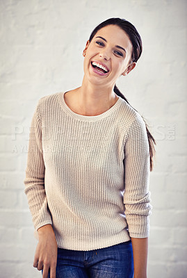 Buy stock photo Portrait of a young woman laughing against a brick wall