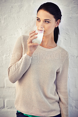 Buy stock photo Shot of a young woman drinking a glass of milk