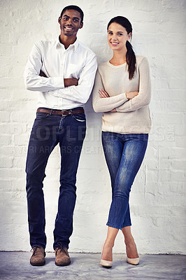 Buy stock photo Portrait of a two casually dressed friends standing side by side against a brick wall