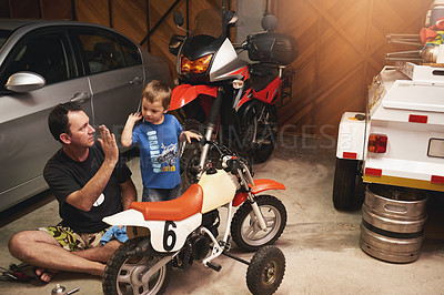 Buy stock photo Shot of a father and son fixing a bike in a garage