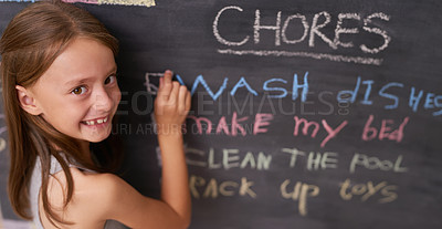 Buy stock photo Portrait of a young girl marking chores off a chalkboard