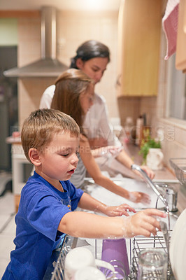 Buy stock photo Shot of a little boy washing dishes with his family at a kitchen sink