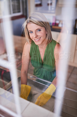 Buy stock photo Portrait of a young woman washing dishes in a kitchen