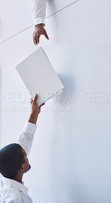 Buy stock photo Shot of a businessman passing on a document to a colleague in an office