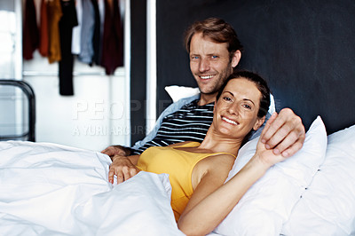 Buy stock photo Portrait of a smiling mature couple lying in bed in the morning