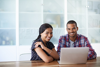 Buy stock photo Portrait of a young couple sitting together at their kitchen table using a laptop