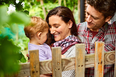 Buy stock photo Shot of a couple with their baby girl standing their organic garden