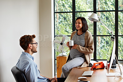 Buy stock photo Shot of a pregnant woman and her husband talking together in their home office