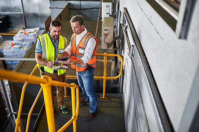 Buy stock photo Shot of two warehouse workers standing on stairs discussing papework