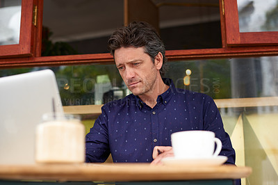 Buy stock photo Shot of a man working on a laptop in a cafe
