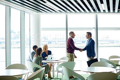 Buy stock photo Shot of a two colleagues shaking hands during a meeting