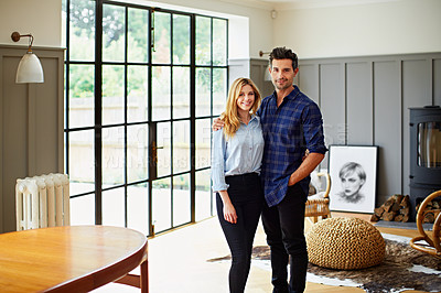 Buy stock photo Portrait of a young couple standing in their living room