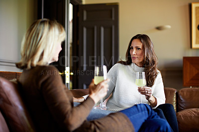 Buy stock photo Shot of a mother and her adult daughter drinking wine and chatting together on a sofa in her living