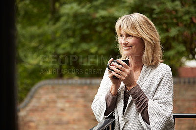 Buy stock photo Shot of a mature woman leaning against the railing of her front porch drinking a coffee