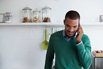 Buy stock photo Shot of a young man talking on his cellphone in the kitchen