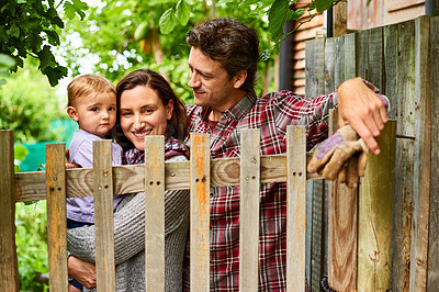 Buy stock photo Shot of a couple with their baby girl standing at the gate to their organic garden
