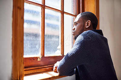 Buy stock photo Shot of a young man deep in though while looking out a window