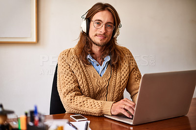 Buy stock photo Portrait of a young designer working on a laptop and listening to music on headphones in an office