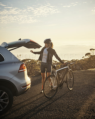 Buy stock photo Full length shot of a young woman taking her bicycle out from the trunk of of her car