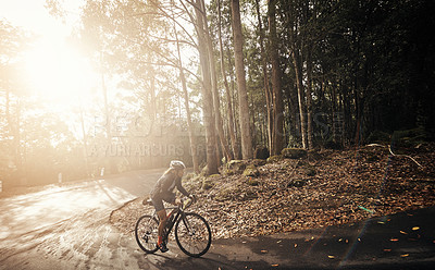 Buy stock photo Full length shot of a young woman cycling in the mountains