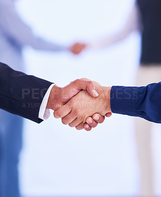 Buy stock photo Cropped shot of two businessmen shaking hands in the office