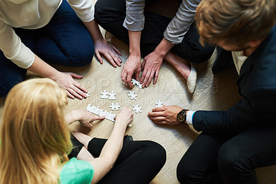 Buy stock photo Shot of a group of people putting a puzzle together