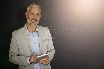 Buy stock photo Portrait of a mature businessman using a digital tablet