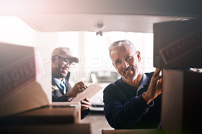 Buy stock photo Shot of delivery men loading boxes into a vehicle