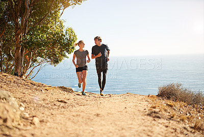 Buy stock photo Shot of a young couple trail running